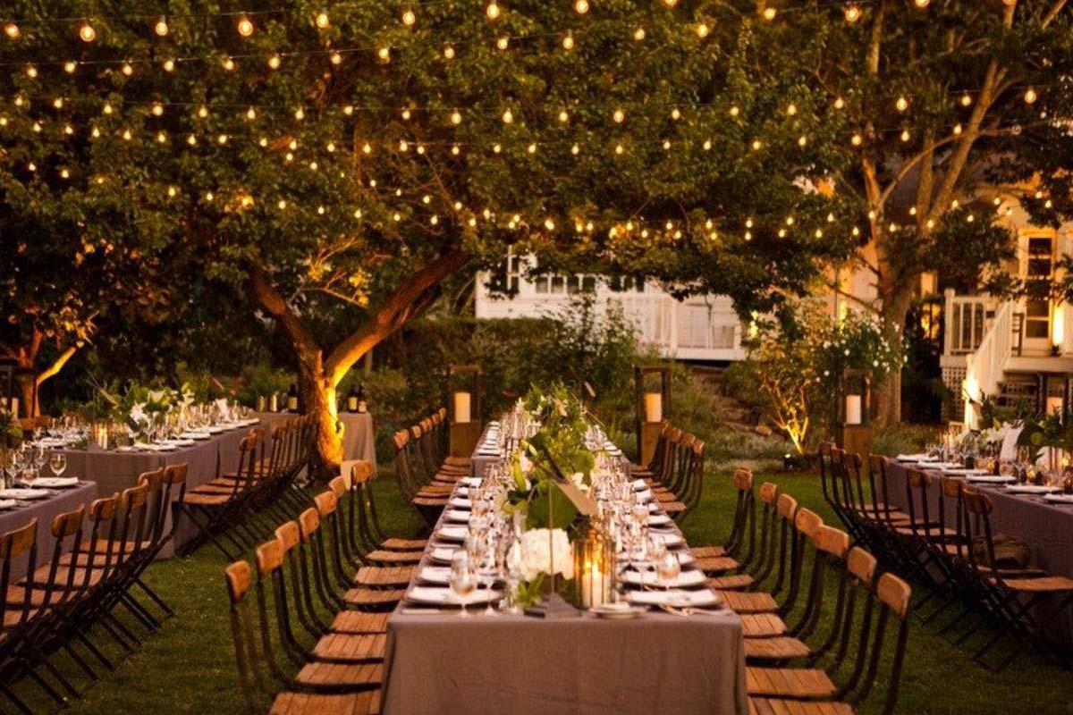 mesas grandes e luzes para casamento no campo