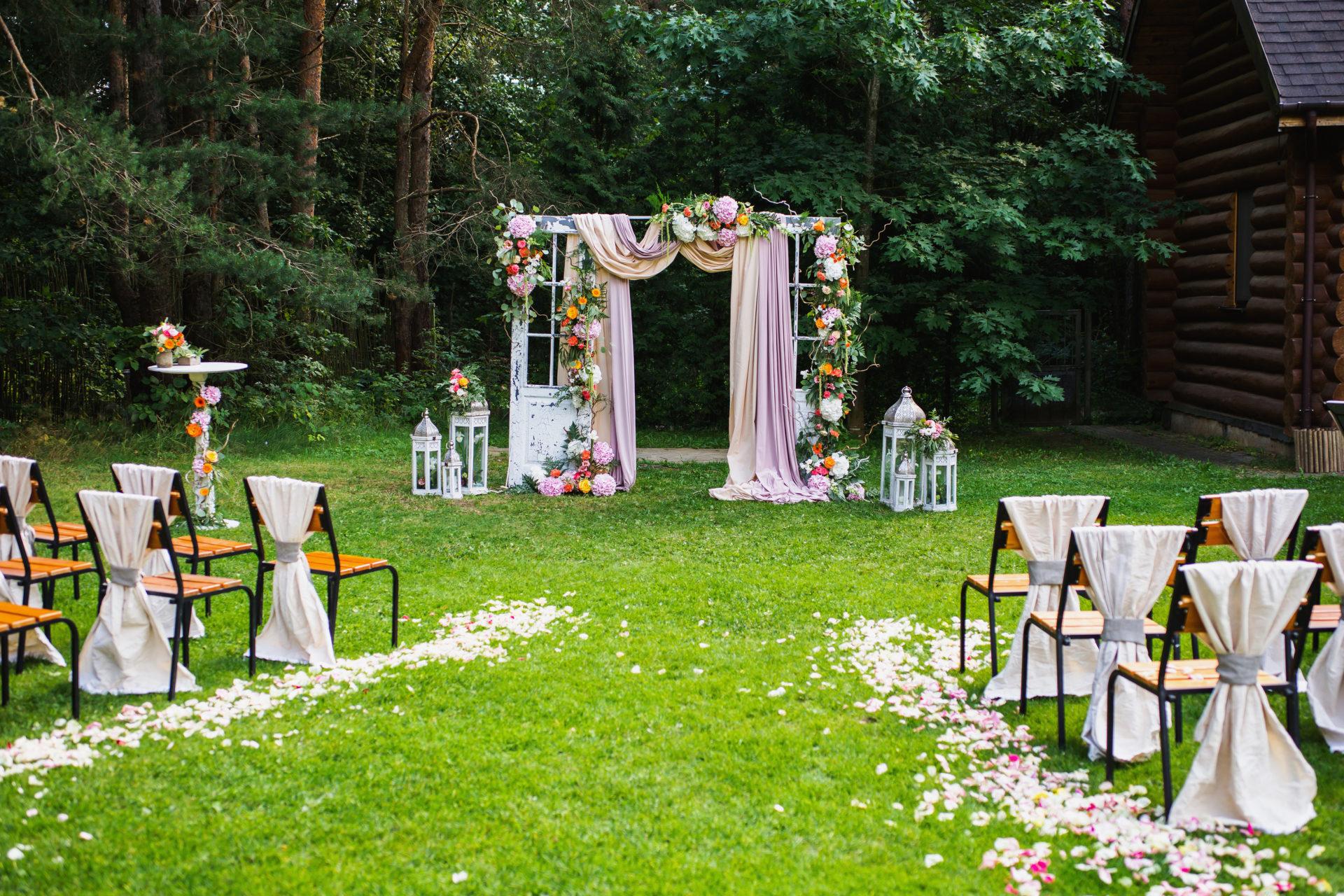 casamento simples no campo com panos rosas, flores coloridas e pétalas de rosas no chão