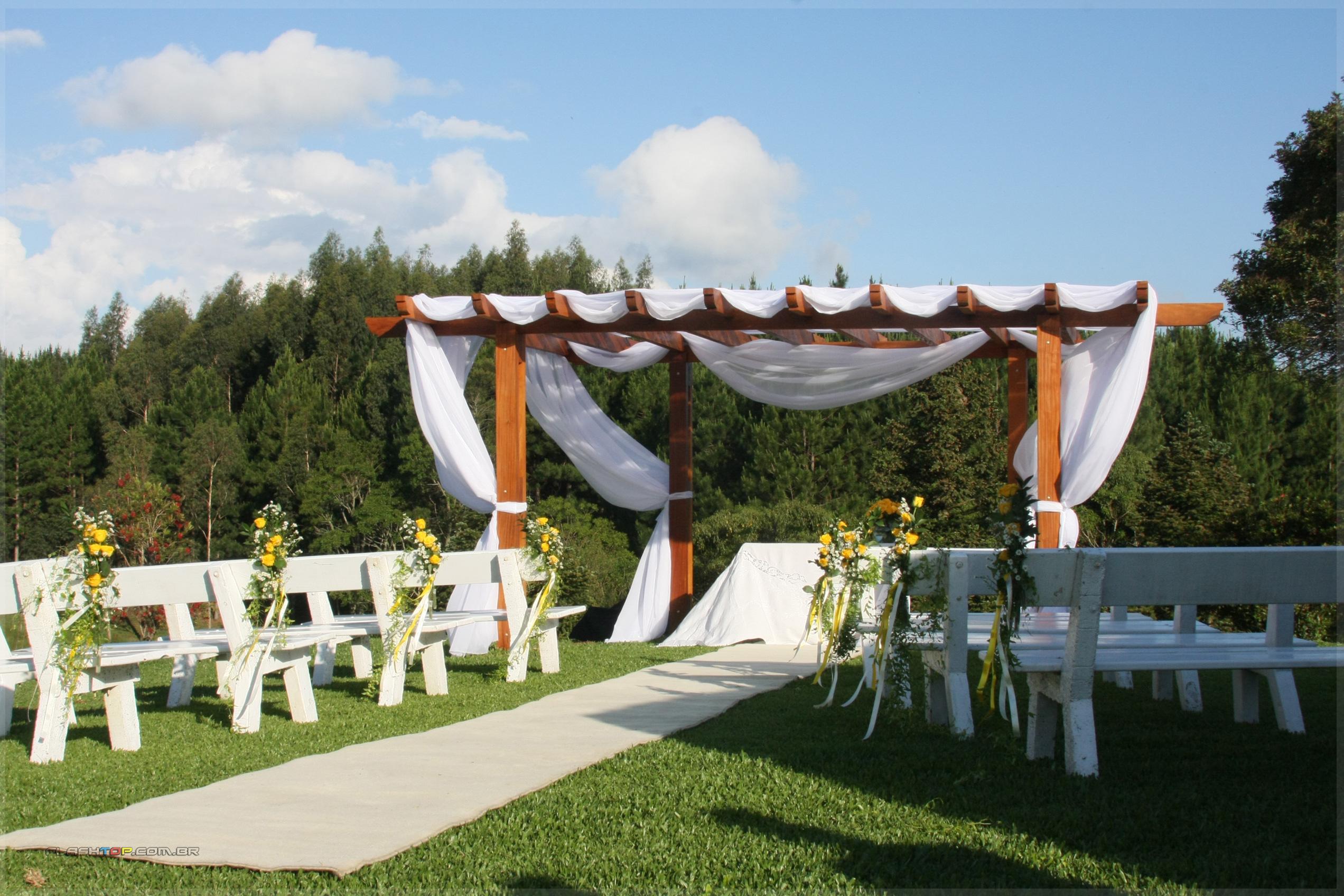 casamento simples no campo com bancos, flores amarelas e panos branco