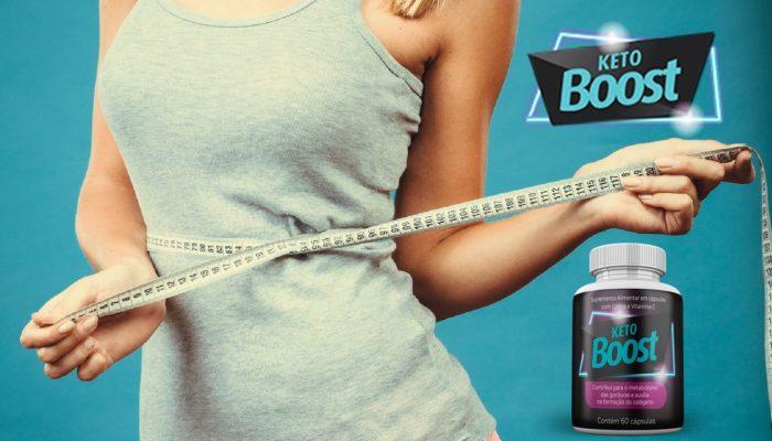 mulher magra segurando fita metrica em volta da cintura e frasco de keto boost ao lado