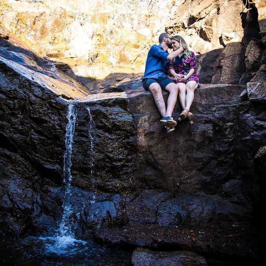homem beijando testa da mulher na cachoeira