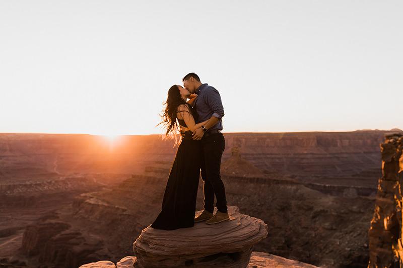 foto casal em cima da rocha com por do sol