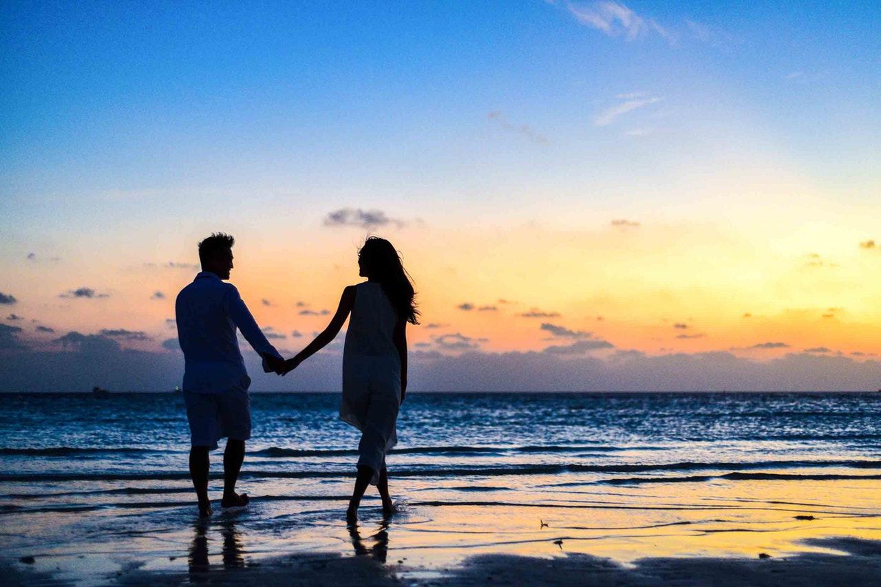casal andando na praia com por do sol