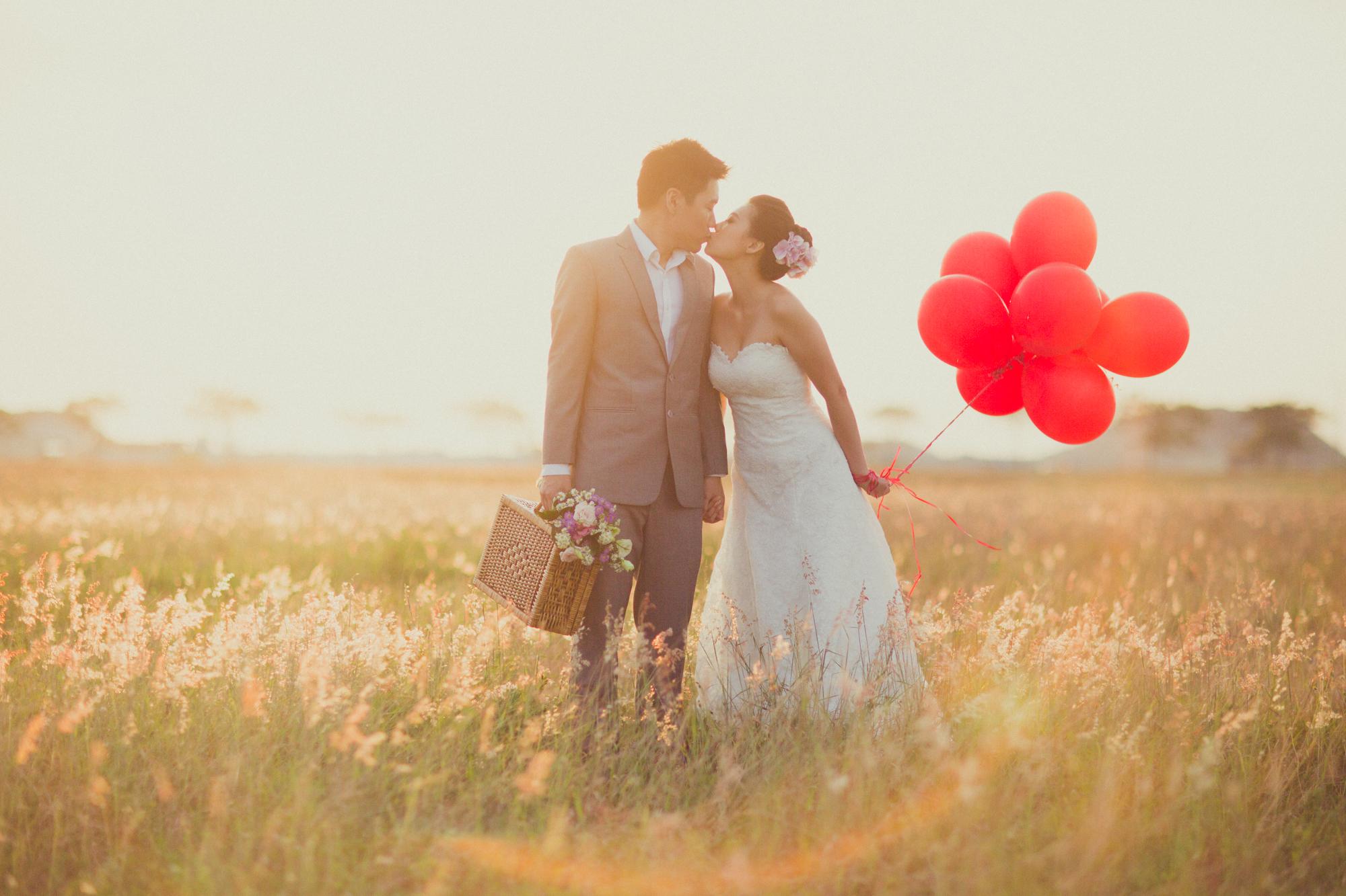 foto no campo para pré-wedding casal segurando balões