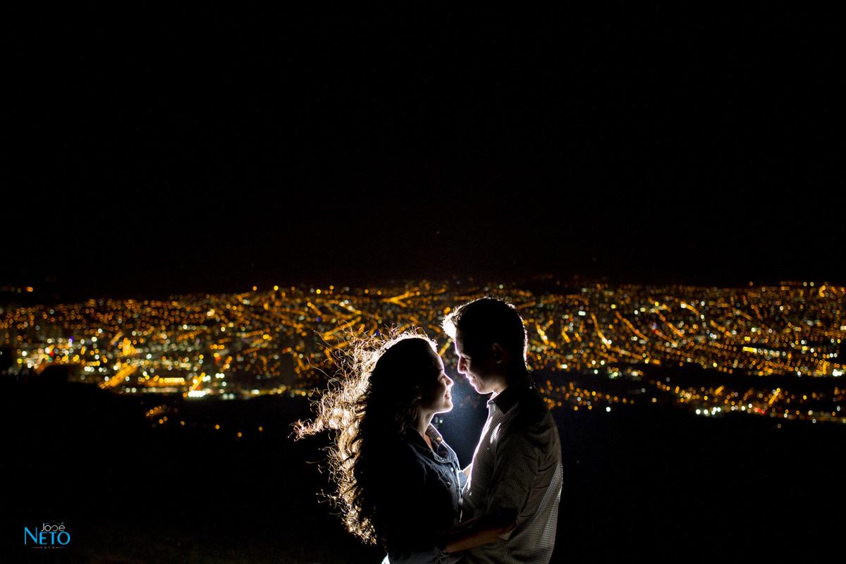 casal tirando foto de noite da vista da cidade