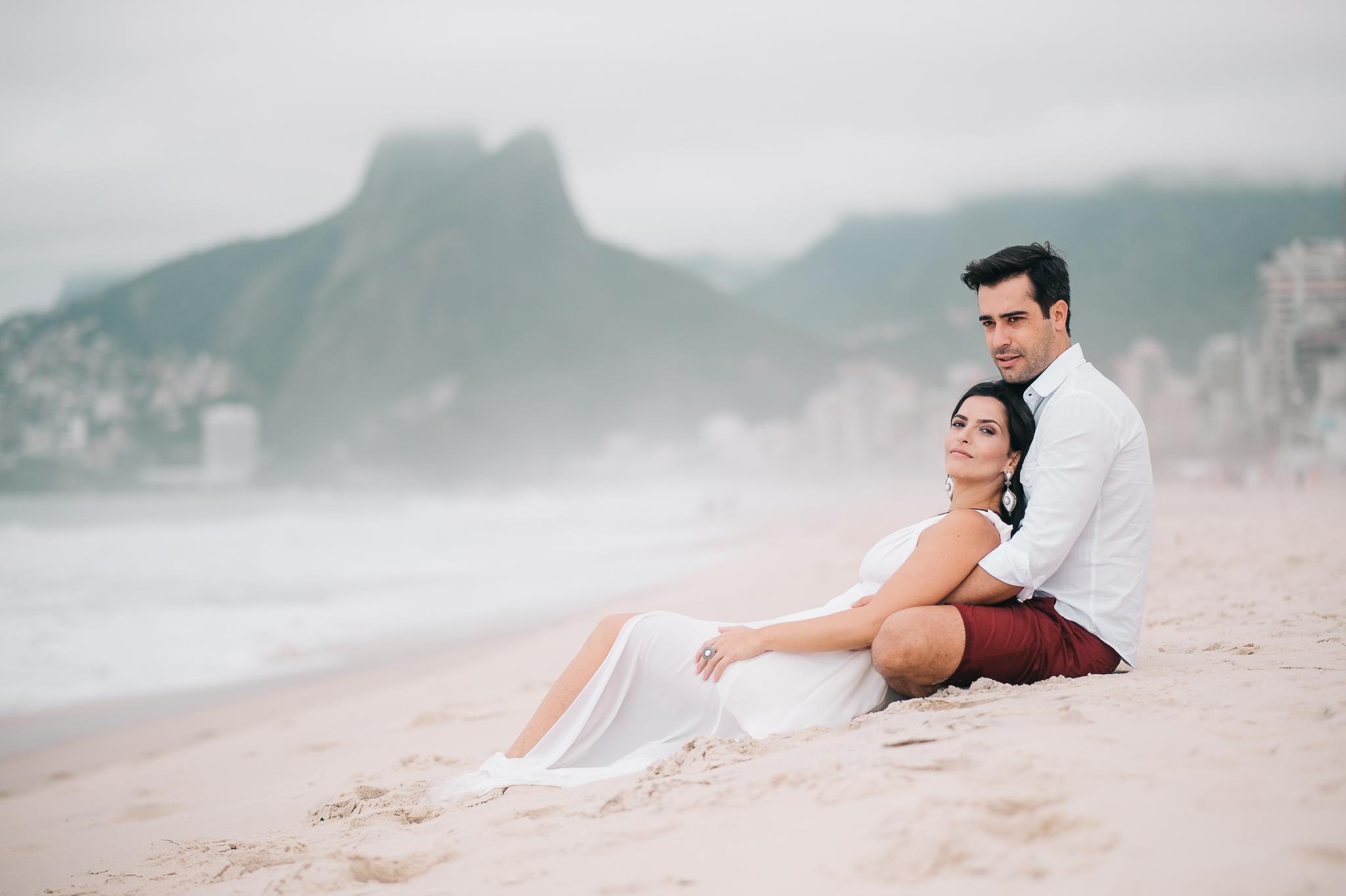 casal sentado na areia para a foto pré-wedding
