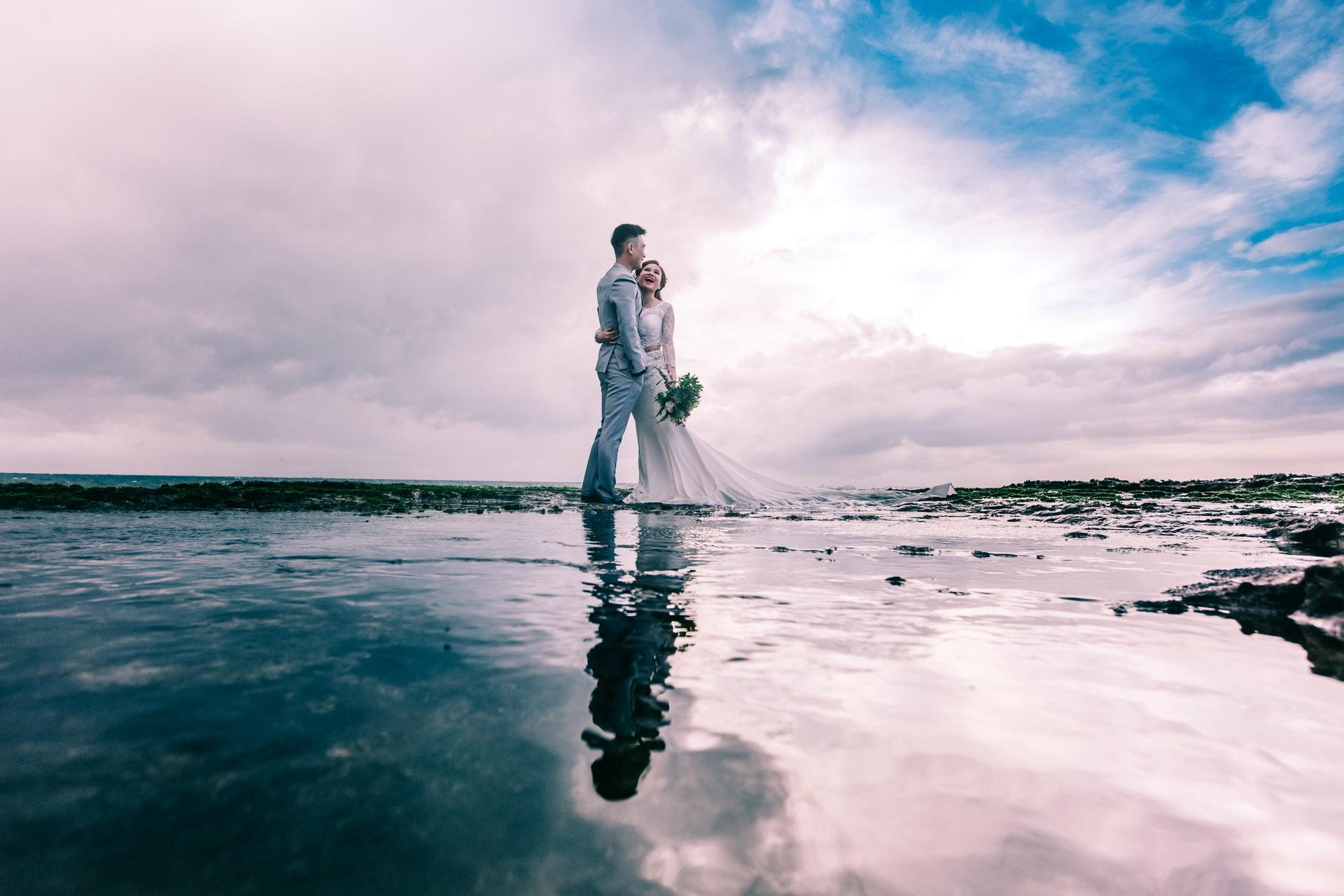 casal com roupa de casamento na praia