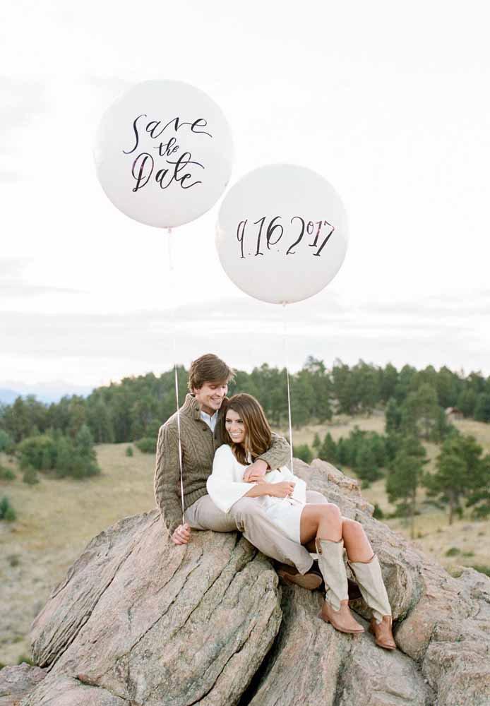 casal no campo segurando balões com a data do casamento