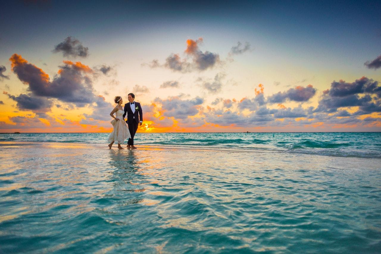 casal correndo na praia com visual do por do sol