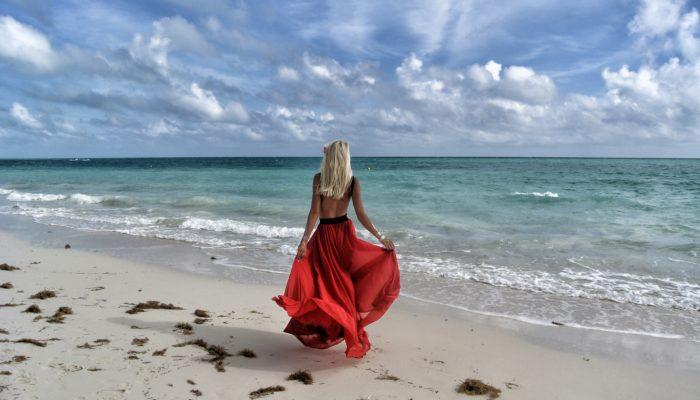mulher na praia com vestido longo vermelho